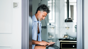 mature businessman with tablet in a hotel room bat P9MVL7Q