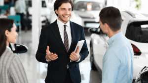 car dealer talking with clients selling them autom XJSXJLH