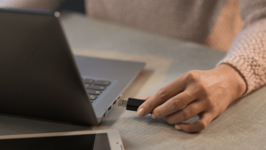 woman plugging a usb flash drive into her laptop WB9C8U4