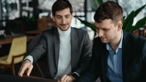 two businessmen pointing laptop screen while discu CC488GR